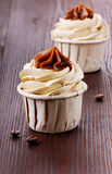 Cupcake with coffee grains. On a brown wooden surface Royalty Free Stock Image