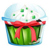 A cupcake container with a green cupcake and a pink ribbon Stock Image