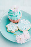 Cupcake and cookies. Butter cream cupcake and cookies with brush embroidery Royalty Free Stock Photo