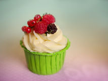 Cupcake with cream cheese frosting decorated with raspberry and redcurrant Royalty Free Stock Images