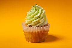 Cupcake with cream isolated on orange Stock Photo