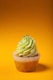 Cupcake with cream isolated on orange background Stock Photo