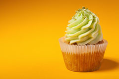 Cupcake with cream isolated on orange background Royalty Free Stock Photography