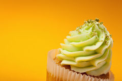 Cupcake with cream isolated on orange background Stock Images