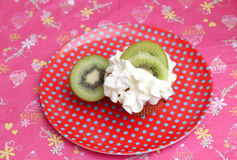 Cupcake with cream. A cupcake with cream and kiwis royalty free stock photo