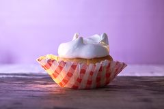 Cupcake with cream on a pastel background on a wooden table Stock Photo