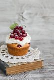 Cupcake with cream and red currants and a book on a light wooden background Royalty Free Stock Photos