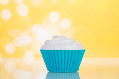 Cupcake with cream on yellow Stock Photography