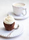 Cupcake with creamcheese icing. And a cup of coffee stock image