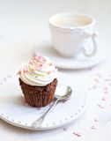 Cupcake with creamcheese icing. And a cup of coffee stock photos