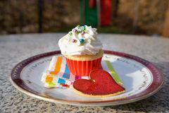 Cupcake or cup cake with whipped cream and small colorfull sugar perils served on the small dessert plate with paper napkin and re Stock Photography