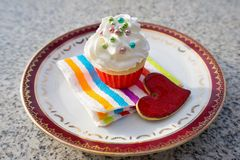 Cupcake or cup cake with whipped cream and small colorfull sugar perils served on the small dessert plate with paper napkin and re Stock Photos