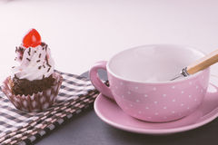 Cupcake with cup, plate and spoon and pink napkin Stock Images