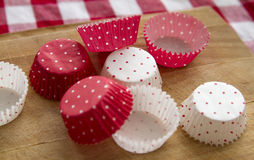 Cupcake cups. Empty cups for cupcakes on kitchen table stock image