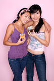 Cupcake Cuties. Two Happy Asian Girls Holding Cupcakes in Studio Royalty Free Stock Image