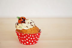 Cupcake decorated with cream and marzipan pumpkin on Halloween Stock Photos
