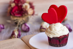 Cupcake decorated with two red hearts on a white plate on the pages of an open book. Postcard or background on Valentine`s Day Royalty Free Stock Image