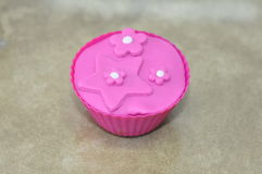 Cupcake with pink frosting. Closeup of a hot, freshly baked cupcake with decorative pink flower frosting or icing Royalty Free Stock Images