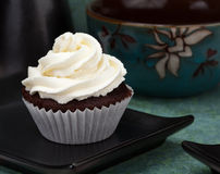 Cupcake Dessert. A Chocolate cupcake with buttercream icing sitting on a black plate royalty free stock photo
