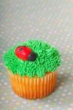 Cupcake die met gras het berijpen wordt verfraaid stock foto