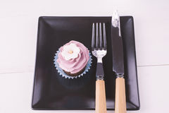 Cupcake and eating utensils on a black plate Stock Photos