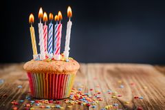 Cupcake with festive lighted candles. On a wooden table stock photo