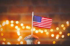 Cupcake and flag of the United States. Homemade classic cupcake and flag of the United States with fairy lights in bokeh stock image