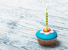 Cupcake with floral decorations and a burning candle. On a wooden table Royalty Free Stock Images