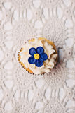 Cupcake with flower decoration, on a vintage doily Royalty Free Stock Images