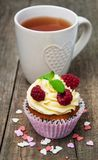 Cupcake with fresh raspberries. On a old wooden table Royalty Free Stock Images