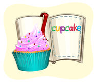 Cupcake with frosting and a book Royalty Free Stock Photos