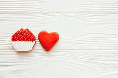 Cupcake and heart icing cookies on white wood, flat lay with space for text. Delicious sweets. Happy Mothers day. Valentine day stock image