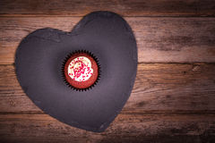 Cupcake on heart on wood Stock Photo