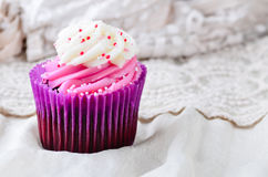Cupcake iced with sprinkles. Royalty Free Stock Image