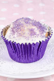 Cupcake with icing and lilac sprinkles Royalty Free Stock Photo