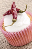 Cupcake with icing and red chili Stock Images