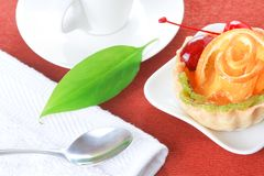 Cupcake with jelly and fruits and a cup of coffee Stock Image