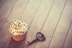 Cupcake and key. On wooden table Stock Photography