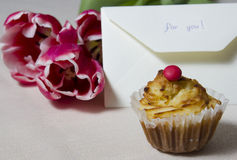 Cupcake with the letter and a bouquet on a table Stock Image