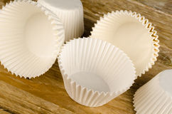 Cupcake liners. Several white cupcake paper liners on a rustic wooden surface Stock Image