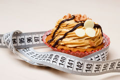 Cupcake with measuring tape on table Stock Image