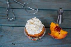 Cupcake met perzikstomp, pijp en kloppers Royalty-vrije Stock Afbeeldingen