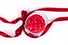 Cupcake met rood suikerglazuur op de transparante die glasplaat met rood lint met een boog op witte achtergrond wordt verfraaid H stock fotografie