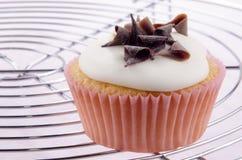 Cupcake met suikerglazuur en chocoladekrullen Stock Foto