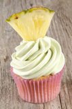 Cupcake with mint buttercream. And a small piece of pineapple Stock Image