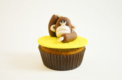 Cupcake with  a monkey figure made of fondant. Funny cupcake with  a monkey figure made of fondant Stock Image