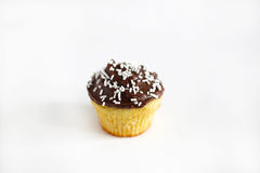 Cupcake or muffin with chocolate icing and sprinkles, isolated Stock Photography