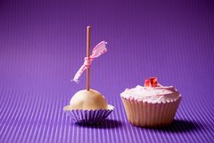 Cupcake and muffin in a pastry isolated on purple background Stock Photos