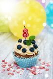 Cupcake with a numeral eight candle Royalty Free Stock Photo