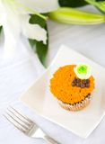 Cupcake with orange icing and green flower biscuit Royalty Free Stock Photography